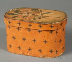 Painted Oval Covered Bandbox, America e.20th C, paper covered wooden box, the top with a lithograph lily, the sides painted with a diamond and cross pattern in red and blue on a pumpkin colored ground, ht. 4 3/4, 8 1/4 x 5 3/4 in.