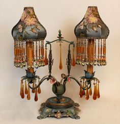 A great pair of 1920s tole candlabra bases with the original amber glass drops hold custom beaded shades dyed gold to green. The Sheik shades are dyed pink to dusty blue-green and are covered in Victorian black net with pink embroidered flowers. Long hand beaded fringe adorns the bottom.