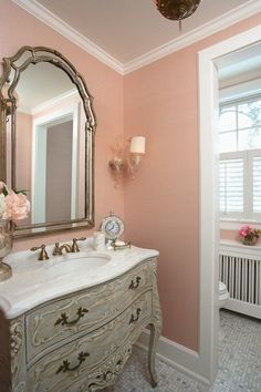 """Love the ornate carved wood vanity in antiqued cream plus the white """"marble"""" lavatory and antique silver-framed mirror in this powder room.  Other colors besides pink would work as well on the walls."""