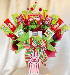 Candy Bouquet for Christmas or Birthday Party...recognize the popcorn bucket used as the base?  Yep, it's from the dollar store!  I've seen these smaller ones come in a pack of two for $1.  Great idea!