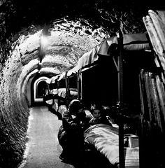 WORLD WAR II: BOMB SHELTER. A woman kneeling beside a girl in a bunk bed in a bomb shelter located in a subway tunnel beneath London England during World War II. Photographed by Tony Frissell. World History, World War Ii, Bomb Shelter, The Blitz, Battle Of Britain, London Underground, Underground Shelter, British History, London History