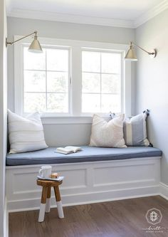 Serena & Lily Dip Dyed Stool beside a reading nook window seat completed with a blue upholstered cushion and various pastel accent pillows. Window Seat Storage, Window Seat Cushions, Window Benches, Window Seats, Porch Bench, Bedroom Reading Nooks, Bedroom Nook, Reading Room, Built In Daybed