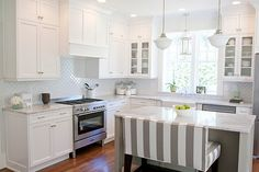 Love the gray and white striped bench. It really stand out against the crisp walls and cabinetry.