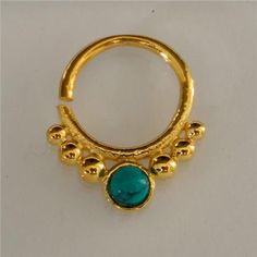 Gold Plated Septum For Pierced Nose - Body Jewelry - Septum Jewelry - Indian Nose Ring - Ethnic Septum - Septum Piercing - Nose Jewelry  New and beautifully made of gold plated brass septum for a pierced nose set with a tibetan turquoise.  Can be wear as an earring as well.  Bar size is 1.2mm. 16 gauge Inner ring 10mm Total diameter 16mm Stone size 3mm $23