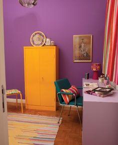 """Já pensou em ter um home office colorido? Aqui, o tom """"purple"""" invadiu a parede e variações dessa tonalidade aparecem em alguns móveis vintage."""