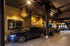 JSPR Gold Crown chandeliers in a garage suspended over an impressive automotive collection. Crown collection is prefect for indoor and and out door use.