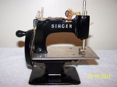 This is a Singer 1950's childs toy Singer Sewing Machine. Description from etsy.com. I searched for this on bing.com/images