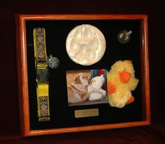 ShadowBoxUSA made this custom shadow box to memorialize Clio, a large Labrador who loved the squeakers in stuffed animals. It contains a photo, clay paw print, collar, small squeaky toy and an engraved plate with text about Clio. By ShadowBoxUSA.com.