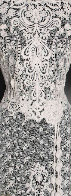 TWO LACE TEA GOWNS, 1905-1908. 1-piece of faux Irish crochet lace, small patterned lace ground w/ heavy raised lace trim on bodice & skirt, group of 3 crochet ball tassels at CFW & CBW. and 1 piece point d'espirit w/ scroll appliques. Detail