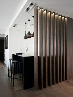 salle de séjour avec un bar noir, salon vaste, chaise de bar taupes, mur taupe, plafond blanc