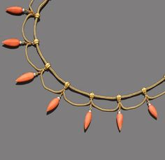 A late 19th century coral and seed pearl necklace. The textured foxtail-link chain, suspending coral amphorae with seed pearl detail, each spaced by similar chain swags, French assay mark, length 39.5cm.