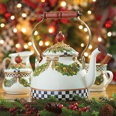 Evergreen Enamel Tea Kettle: MacKenzie-Childs introduces new serving pieces to its stunning collectible enamelware, which is sure to become a perennial favorite during the season of nostalgia. Each piece is decaled with tartan plaid ribbons and golden apples, with greenery of blue spruce, red cedar, Scots pine, live oak, and holly.