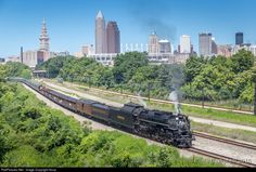 The ghosts of the steam railroading era are being stirred as 765 and her train cross the Cuyahoga River Bridge and charge down the old NKP main. The Cleveland Union Terminal in the background was once a bustling passenger hub for many roads including the Nickel Plate, and also housed their corporate offices. As the whistle echoed across downtown, everyone watching was silenced with reverence, awe and whatever other emotion this sensory spectacle elicited.