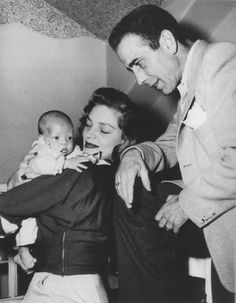 Humphrey Bogart and Lauren Bacall show off their first-born son, Stephen, to anxious photographers. (1949)