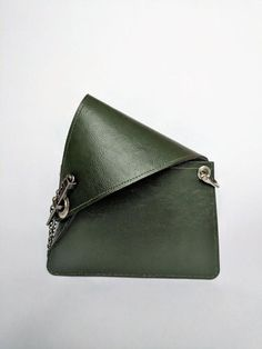 Vegan crossbody bag in forest green/pale pink with unique sculptural, asymmetric design and pin clasp closure. It looks small and cute, but its big enough to fit wallet, keys, phone and sunglasses. Available with either crossbody-length chain or faux leather strap. Accessorize with the dodecahedron