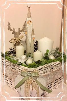 Centrotavola realizzato con candele, muschio, fiori artificiali, palline natalizie, oggetti in legno.