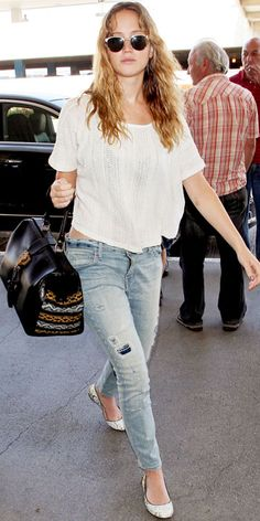 Jennifer Lawrence arriving at LAX wearing a crop top paired with Current/Elliott distressed skinnies. She accessorized with Leisure Society sunglasses, a Cobra Society bag and Rachel Zoe Collection ballet flats.