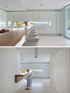 This kitchen has a letterbox window that provides picturesque views of the surrounding area, and a long wooden bar breaks up the all-white kitchen.