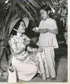 "Th text on the back of the photo reads:.  .  ""Vice president Richard M. Nixon made the first contribution to Foster Parents Plan's Vietnamese shoe campaign and nine year old To Thi Ngoc of Saigon, Vietnam receives the first pair of shoes from Plan staff member, Voung Thi Thiet, in a special ceremony in Saigon, Vietnam."""