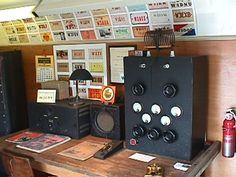 FeatureStation: From the left: A 1932 Hammarlund Comet Pro receiver, speaker, coil box and the QSL card of the first owner Dare Aucott, W3CRY, of Atlantic City, NJ.   Right: Key on black-wooden base and well-made homebrew 300 watt transmitter built by Joe Hoffman, W2DST of New York.  Table and wall: the 1933 station license, his first log, lamp and chair of Earl Abbott, W2FTT, Manahawkin, NJ, and a collection of 1930's QSL cards from southern New Jersey.  The 1930's brass key was presented…