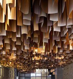 faux plafond bois suspendu avec lampes de plafond dissimulées et murs en béton gris