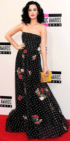 "Katy Perry wearing a strapless polka-dot Oscar de la Renta ball gown embroidered with flowers, with an over-sized floral cocktail ring and a yellow ""dictionary"" Charlotte Olympia box clutch."