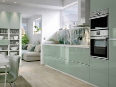 A medium size kitchen with light green high-gloss doors and drawers combined with stainless steel handles and appliances. Shown together with a wall panel with a blue-green cloud pattern.