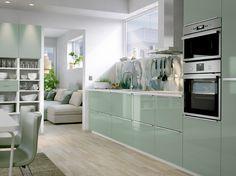 Cuisine de taille moyenne avec portes et tiroirs en vert clair brillant, poignées et appareils en acier inoxydable. Un panneau mural orné d'un motif de nuage bleu-vert complète l'ensemble.