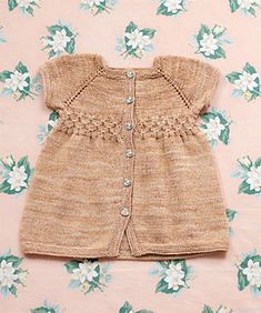 This dress is knit from the top down so the length can be customised. The buttons can be at the front or back. As baby grows bigger it could be worn as a tunic top.