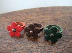 #52の革かごバッグと同じ革ひもと同素材の花型革パーツを発見。革ひも+花型パーツだけで簡単にできるものを試作しました。指のサイズに合わせて革ひもを切り穴をあけて、ブラッズを花芯代わりに通して留めているだけの簡単なリングです。花型パーツが薄手