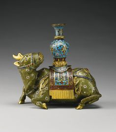 A RARE CLOISONNE ENAMEL FIGURE OF A QILIN QIANLONG MARK AND PERIOD the animal recumbent with tail curled alongside its haunches, the head well-cast with a single gilt horn, slightly raised and turned characteristically over the back, presumably to gaze at the moon, elaborately caparisoned and bearing a turquoise ground baluster vase on its back, its body brightly enameled in sage-green accentuated with gilt 'fur' and florets