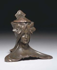 ART NOUVEAU COLD-PAINTED INKWELL modeled as the head of a maiden with flowers in her hair, with hinged lid and glass reservoir 5 5/8in. (14.3cm.) high