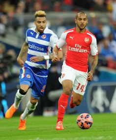 Theo Walcott of Arsenal takes on Daniel Williams of Reading during the FA Cup Semi Final at Wembley Stadium on April 18, 2015.