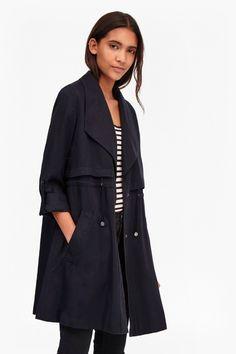 "<ul> <li> Lightweight tencel trench coat with storm lapels</li> <li> Soft-handle fabric</li> <li> Turn-back sleeves with adjustable straps</li> <li> Two slanted, slip pockets</li> <li> Adjustable, waist-defining drawcord waistband with toggles</li> <li> Metallic snap fastenings</li> <li> Oversized fit</li> <li> UK size 10 length is 89cm</li> </ul>  <strong>Our model is 5ft 10"" and is wearing a UK size 8. </strong>"