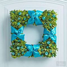 A few bows and baubles add festive style to this modern, not-too-Christmassy wreath. Start with a purchased boxwood wreath, or make your own from fresh boxwood greenery by clicking below. To decorate, cut 8 strips of ribbon long enough to wrap around the wreath. Lay out 2 pieces of ribbon in an X-shape. Wrap a small length of floral wire around the middle of each X; twist ends together in back to secure. Nestle wire into the wreath as you wrap ribbon around wreath. Glue ribbons ends in…