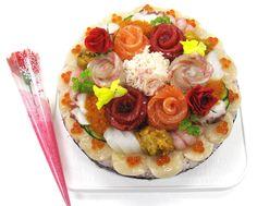 Real sushi cake made with sashimi and sushi on a rice cake.