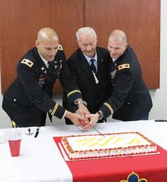 """Col. Joseph S. Pina, Kenner Army Health Clinic commander, Howard Mosier and Col. Edward M. Daly, Chief of Ordnance and commandant of the U.S. Army Ordnance School cut a cake at a reception following the dedication of Mosier Troop Medical and Dental Clinic. Howard Mosier is the brother of Corp. William Clarence """"Billy"""" Mosier, a decorated Korean War hero whom the clinic is named after."""