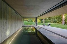 Located in East Sussex, the Red Bridge House by Smerin Architects houses a minimalist pool on the lower level where it opens up completely to an outdoor terrace overlooking a stream.Photo by Tim Crocker Indoor Swimming Pools, Swimming Pool Designs, Indoor Outdoor Pools, Lap Pools, Backyard Pools, Pool Landscaping, Building A Pool, Building A House, Build House