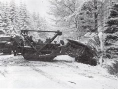 An engineer employs a bulldozer to topple a German armored vehicle into the woods.
