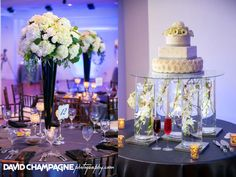 three-tier wedding cake with glass vase risers #square #round #realweddings Tamra & Vontae in The Coastal Room.  ❘The Yacht Club at Marina Shores #waterfront #weddings #virginiabeach @yachtclubatms
