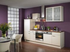 Purple doesn't have to be slick and minimalist to work; this kitchen pairs it with cream and modern furniture for a more comfortable and cosy room.