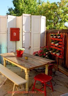 Look at the upcycling here with re-purposing folding doors as a wall divider, the gorgeous red painted accents, and a planter wall to liven this outdoor nook up!