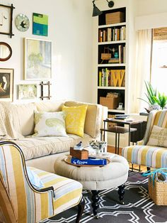 I love the fresh happy feel of this room. I've had my eye on it for a long time. Love the striped chairs, the gallery wall, the round ottoman, the lights above the bookshelves (painted dark inside!). And, the rug is awesome too!