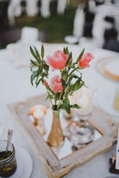 Petite centerpiece and candles on a vintage framed mirror.