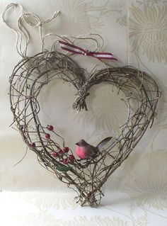 A heart symbol craft using wires and other materials. The gray wires varying from thin to thick sizes have been joined together to form a heart. To finish the effect a ribbon is tied on top and a bird standing on top of a twig with berries.