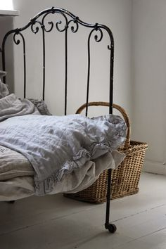 Iron bed with linen coverlet