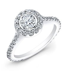 """ENG-5518A - This 14KT white gold engagement ring features a halo design with 69 prong-set round diamonds. The bezel-set center stone weighs 1.36CTS and is a round brilliant diamond. See its matching band under """"Related Products"""" below."""