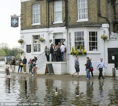 People leave and arrive at the The White Cross pub at the high tide entrance Richmond Upon Thames, Uk Weather, St Margaret, People Leave, Desert Island, White Crosses, High Tide, River Thames, Beautiful Sunrise