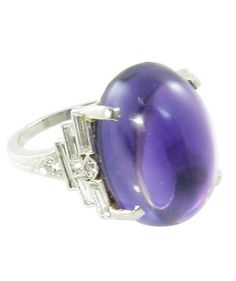 An Art Deco platinum, amethyst and diamond ring, Durand  Company, Newark, New Jersey, circa 1920. Signed with Durand  Company's maker's mark and irid plat. The ring is set with a center large oval cabochon amethyst, flanked on each side with 5 collet set baguette diamonds and 3 round single cut diamonds in a graduated geometric pattern