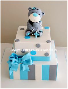 Christening design featuring Tatty Teddy Bear holding rosary beads on a beautifully designed 2 tiered sharp edged square cake. Can be designed for a boy or girl.